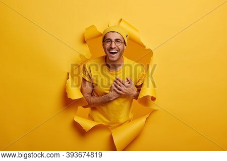 Satisfied Man Stands In Paper Hole, Keeps Hands Near Heart, Expresses Gratitude, Being Pleased By He