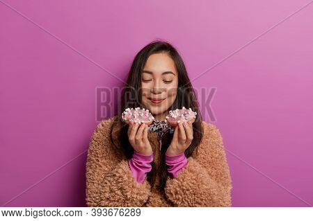 Photo Of Sugar Addicted Woman Smells Freshly Baked Donuts, Impossible To Resist Eating Dessert, Read
