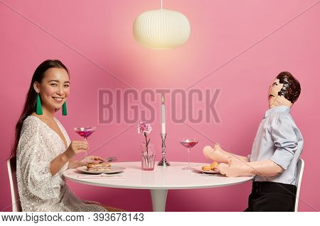 Horizontal Shot Of Beautiful Woman In Festive Clothing Holds Glass Of Cocktail, Meets With Man In Re