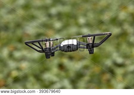 Hovering Black And White Photo Drone With Four Rotor Blades Flying In The Air Against A Green Backgr