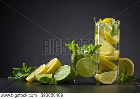 Cocktails With Lime , Lemon , Ice And Peppermint Leaves On A Black Table .copy Space.