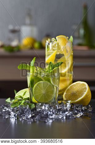 Cocktails With Lime , Lemon , Ice And Peppermint Leaves On A Black Table .