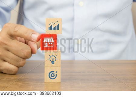 Close-up Hand Chooses Cube Wooden Toy Blocks Stacked With Franchise Business Store Icon. For Small B