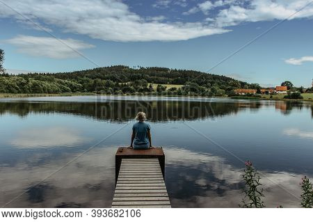 Beautiful Young Girl Meditating By Lake. Practicing Yoga Outdoors. Harmony And Meditation Concept.he