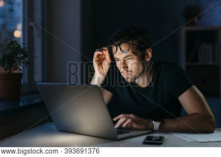 Overworked Tired Man Student Freelancer Works Remotely With Laptop At Night, Holding Glasses Feel Ey
