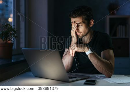 Young Businessman Has Headache While Working Overtime With Laptop At Home Office Late Night. Stresse