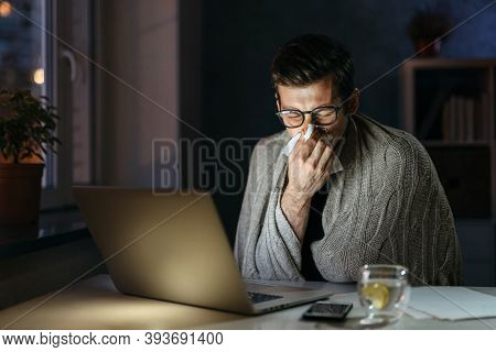 Sick Businessman Blowing Nose While Working On Computer In Home Office At Night. Young Man Sneezing