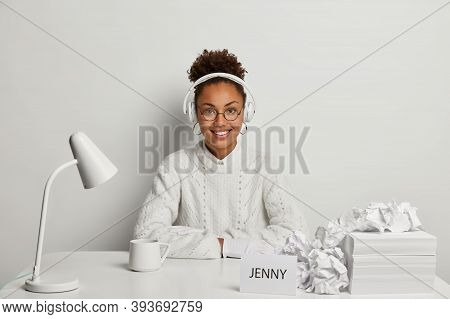 Smiling Curly Afro American Woman In White Jumper, Wears Headphoes On Ears, Listens Relaxing Music,