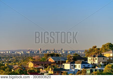 Set Of Houses With Adelaide City Skyline View On Background At Sunset, South Australia