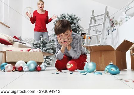 Merry Christmas And Happy Holidays! Mom And Son Decorate The Christmas Tree Indoors. Accidentally Th