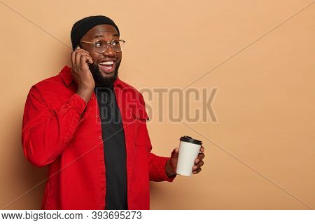 Bearded Glad Young Man Has Phone Conversation With Best Friend, Holds Mobile Phone, Drinks Aromatic