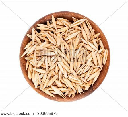 Unpeeled Oat Grains In Wooden Bowl, Isolated On White Background. Organic Dry Oat Seeds. Top View.