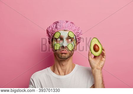 Photo Of Handsome Man Has Rejuvenation Facial Treatment, Holds Avocado, Applies Fresh Cucumber Slice