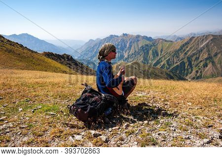 Young Trekker Man Resting And Playing Guitar In Rocky Pass With Mountain Top Wiews In High Mountains