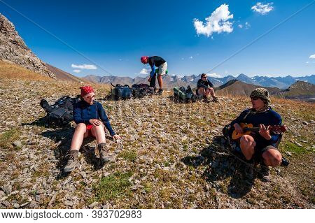 Group Of Trekkers Resting And Playing Guitar In Rocky Pass With Mountain Top Wiews In High Mountains