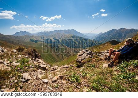 Young Trekker Man Resting In Rocky Pass With Mountain Top Wiews In High Mountains. Young Men And Wom