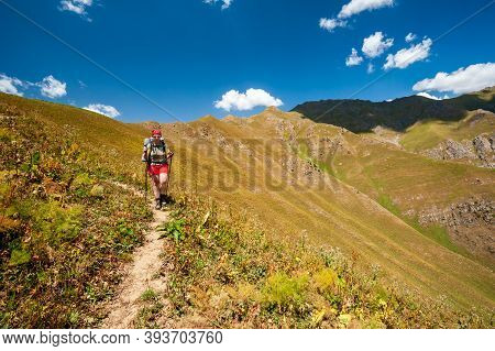 Female Hiker. Young Woman Alone Trekking And Backpacking In High Mountains Near Sary Chelek Lake, Sa