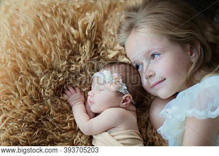 Little Caucasian Girl And Her Newborn Sister. Toddler Kid Meeting New Sibling. Cute Girl And New Bor