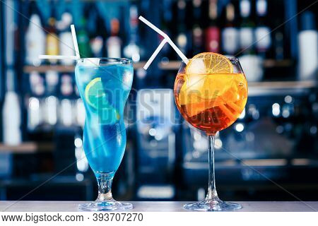 Blue Lagoon Cocktail And Aperol Cocktail At Bar Counter Background. Soft Focus, Selective Focus