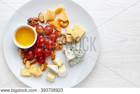 Cheese Plate Served With Grapes And Nuts. Assorted Cheeses Camembert, Brie, Parmesan Blue Cheese, Go