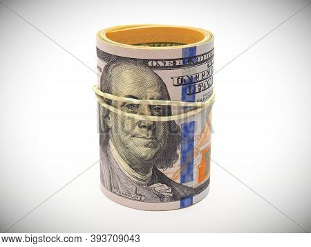 A Bundle Of New-style 100 Dollar Bills Is Rolled Up, Tied With An Elastic Band And Placed On A White