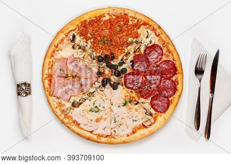 Whole Pizza With Four Different Type Of Toppings On A White Table With A Napkin, Knife And Fork. Top