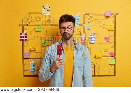 Puzzled Bearded Male Artist Looks At Red Paint Brush, Makes House Renovation, Wears Shirt, Redecorat