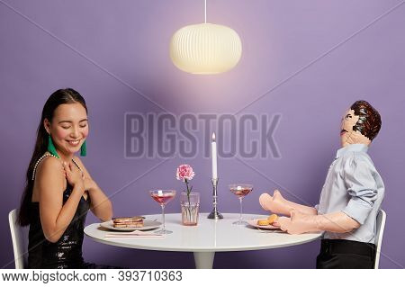 Touched Woman Pretends Receiving Heartwarming Compliment From Lover, Sits At Table With Layman Doll,