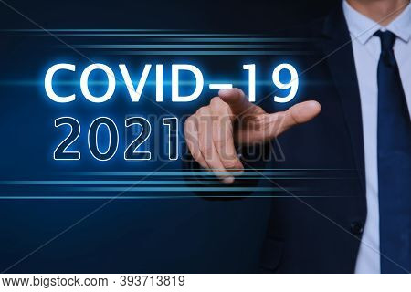 Covid-19 Predictions For 2021 Year. Man Touching Virtual Screen On Dark Background, Closeup