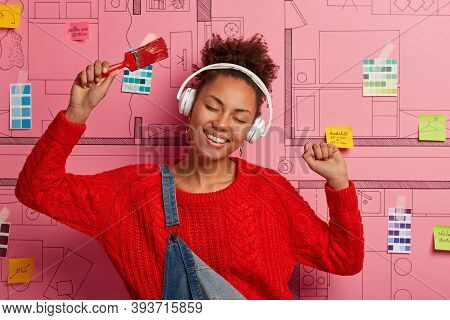Amused Relaxed Woman Dances Happily, Raises Arms With Paint Brush, Listens Music In Wireless Headpho