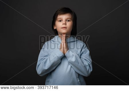 Portrait Of Boy 10-12 Years Old In Casual Clothes Keeping Palms Together And Praying. He Meditating,