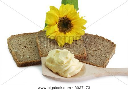 Brown bread with oleo on a cooking spoon and sunflower poster