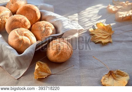 Kaiser, Or Vienna Buns In Bread Basket On Textile Background With Yellow Autumn Leaves.