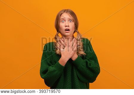 Image Of Blonde Girl 12-14 Years Old In Warm Green Sweater Expressing Fear And Horror. Studio Shot,