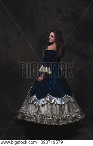 Beautiful Woman In Renaissance Dress On Abstract Dark Background