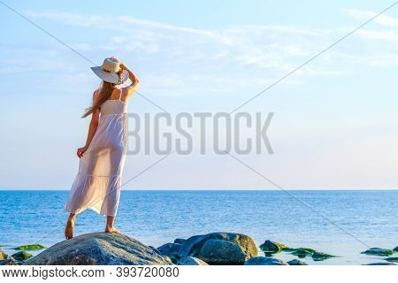 Back view of anonymous carefree female tourist in dress and hat standing on rock and enjoying scenery of sea during summer holiday