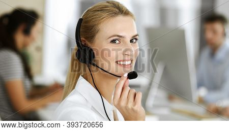 Blonde Business Woman Using Headset For Communication And Consulting People At Customer Service Offi