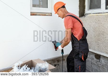 Insulation Of The House With Polyfoam. The Worker Is Drilling Holes To Fix The Styrofoam Board On Th