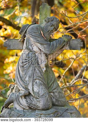 The Man Hold Wooden Cross, Graveyard Statue On Tombstone. 24th Of October 2020. Hronov, Czechia.  He