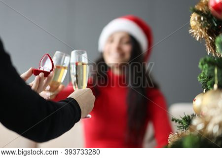 Man Holding Wedding Ring In Box And Drinking Champagne With Woman In Santa Claus Hat On New Years Ev