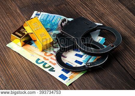 Gold Bullions With Handcuffs On Euro Banknotes, Financial Concept Of Handcuffs And Gold Bars On Euro