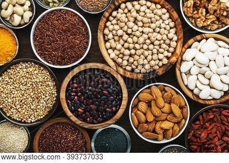 Superfoods, Legumes, Nuts, Seeds And Cereals Set In Bowls On Wooden Background. Superfood As Chia, S