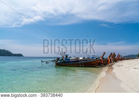 Traditional Long Tail Boats In Crystal Clear Water In Sai Khao Beach, Ra Wi Island, Southern Of Thai
