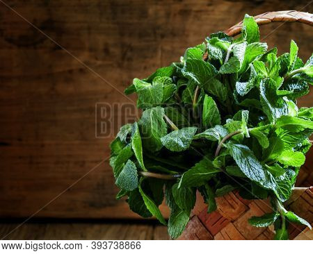 Bunch Of Peppermint In A Wicker Basket, Vintage Wooden Background, Selective Focus