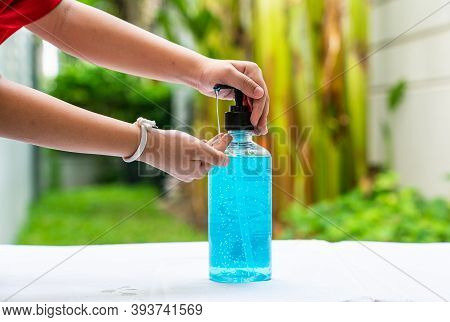A Boy Using Alcohol Hand Cleansing Gel To Clean His Hand.
