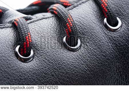 Close-up View Of Red Black Shoelaces On Leather Boot. Casual Fashion Concept. Selective Focus.