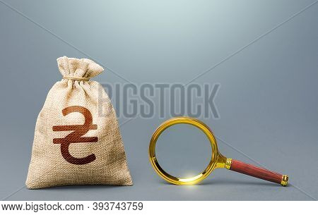 Ukrainian Hryvnia Money Bag And Magnifying Glass. Origin Of Capital And Legality Of Funds. Most Favo