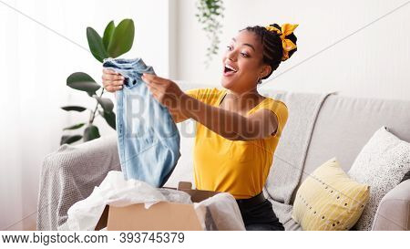 Delivery Concept. Smiling Black Woman Holding New Jeans, Unboxing Cardboard Package, Sitting On The