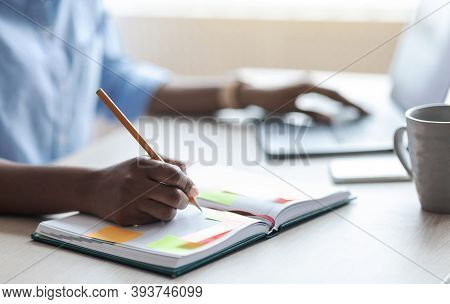 Busy Unrecognizable Woman Writing In Notepad, Taking Notes At Workplace In Office, Using Laptop Comp