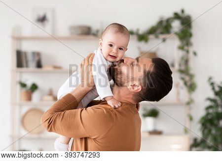 Dads Love. Cute Young Father Kissing His Little Baby Daughter Cuddling And Bonding Holding Newborn T